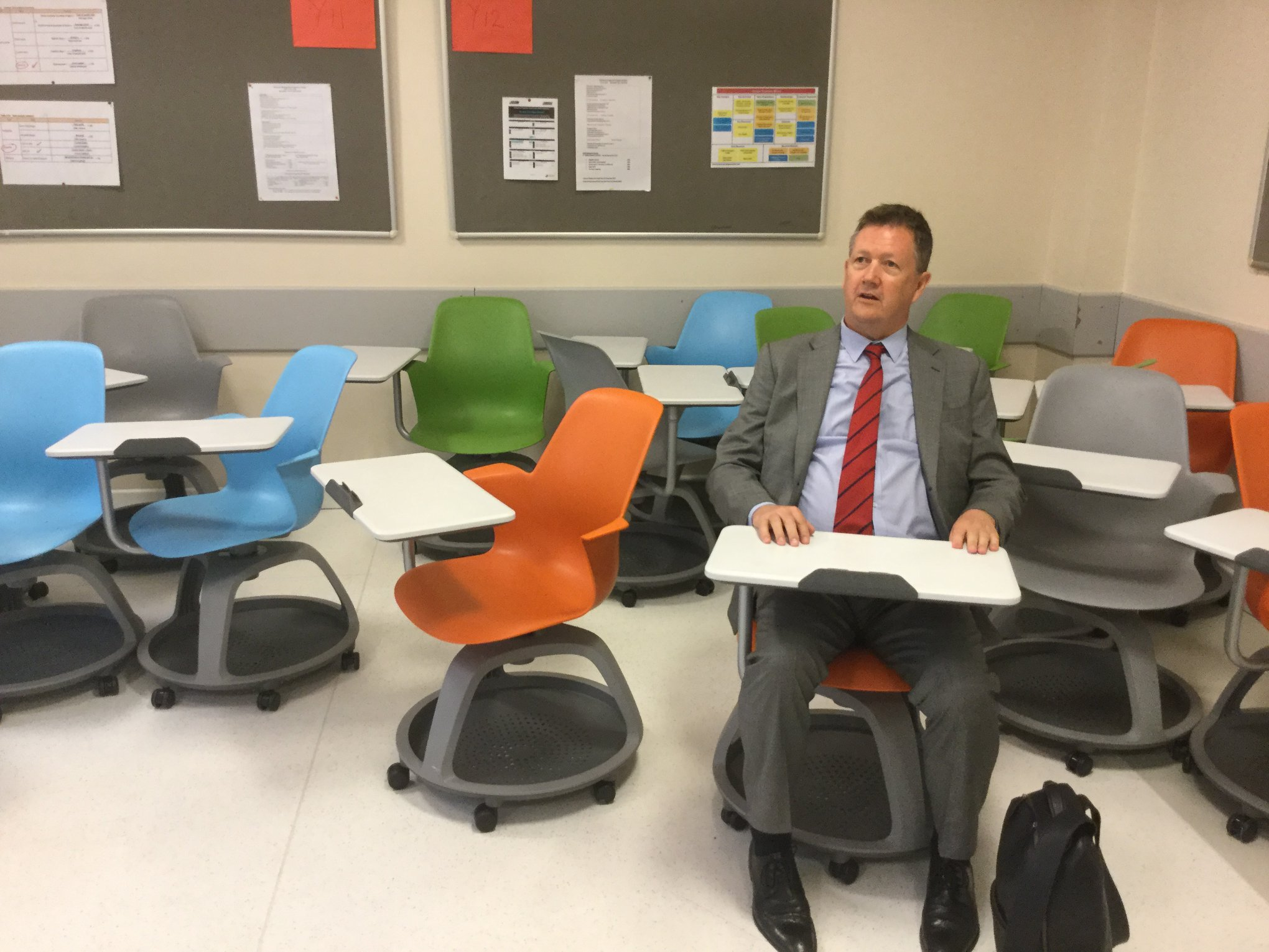 Bill tries out a colorful student desk at The KOC School, Istanbul